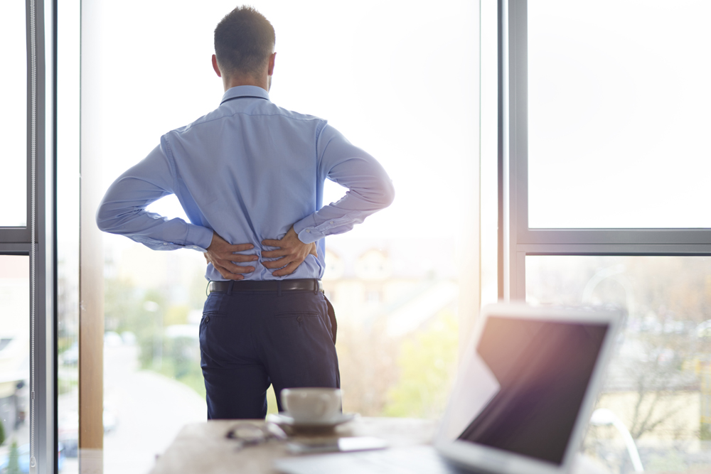 man at work holding his back in pain due to a work injury from poor ergonomics