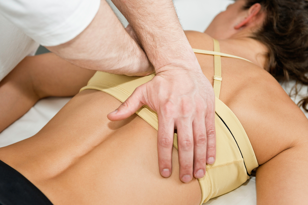 chiropractor with patient during a chiropractic exam for a back adjustment